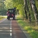 Trekker (Valtra) komt met werktuig tegen bomen aan