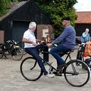 Scootmobielgebruikers bekijken antieke fietsen